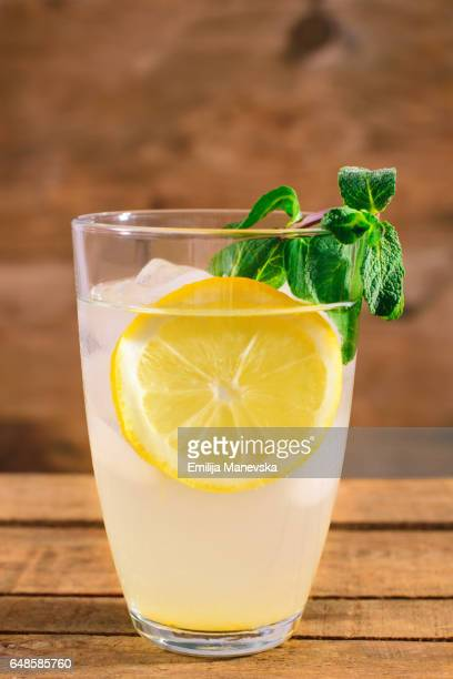 Lemon juice with fresh mint leaf on wooden background