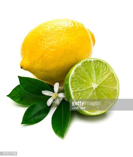 Lemon, lime and green leaves against white background