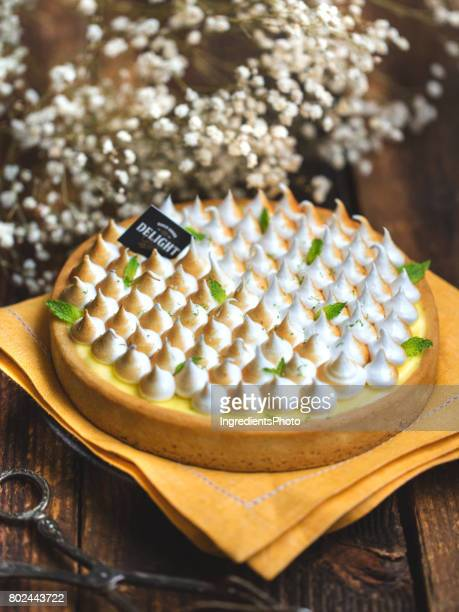 Lemon meringue tart on a rustic wooden table.
