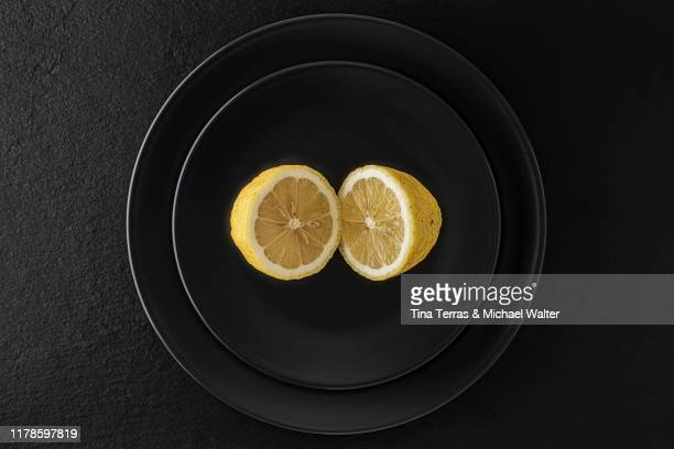 a  lemon on a black plate. the plate is standing on a black slate plate. - bisected stock pictures, royalty-free photos & images