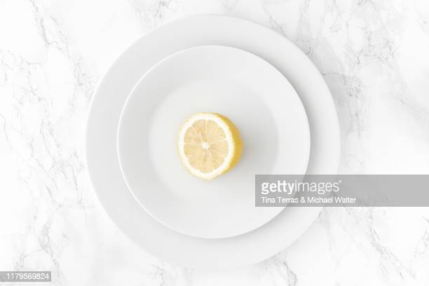 lemon on white plate. bright background. minimalism. - roundel stock pictures, royalty-free photos & images