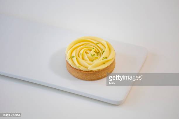 lemon pie on a white plate with rose shape cream decoration - mousse dessert stock pictures, royalty-free photos & images