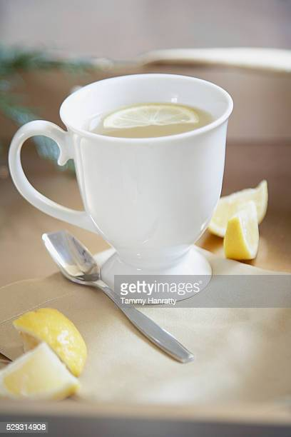 Lemon slice floating in coffee cup