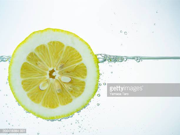 Lemon slice floating in water, surface view, close-up