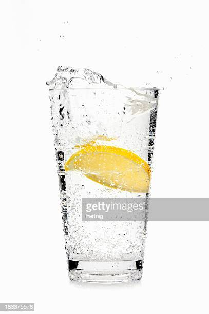 Lemon slice splashing into soda water