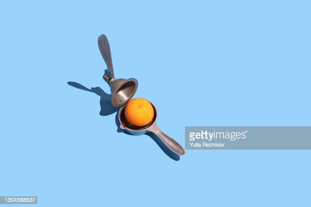 lemon squeezer and blood orange on the blue background - image stock pictures, royalty-free photos & images