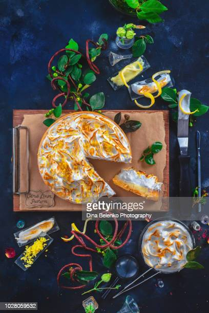 Lemon tart with meringue, leaves and botanist tools on a dark background. Pastry herbarium with wooden clipboard and laboratory glassware. Dessert anatomy concept