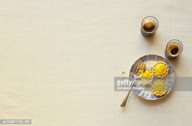 Lemon tarts on plate next to two cups of coffee, directly above