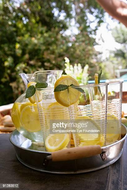 Lemonade and glasses on metallic tray