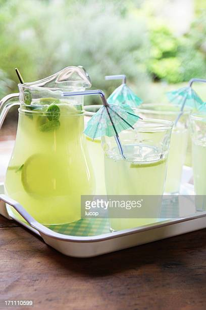 Lemonade cocktail with umbrella drinking straws at garden