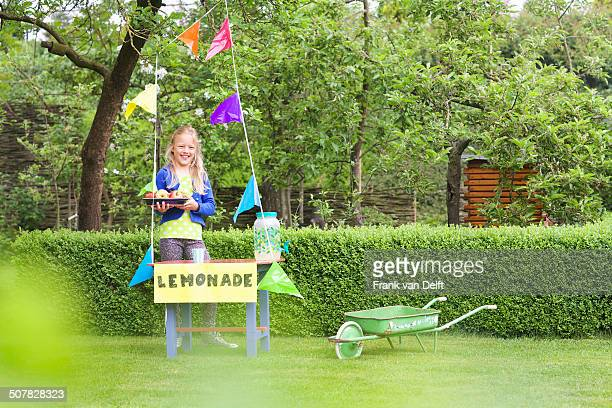 Lemonade stand girl with tray of apples behind her stand