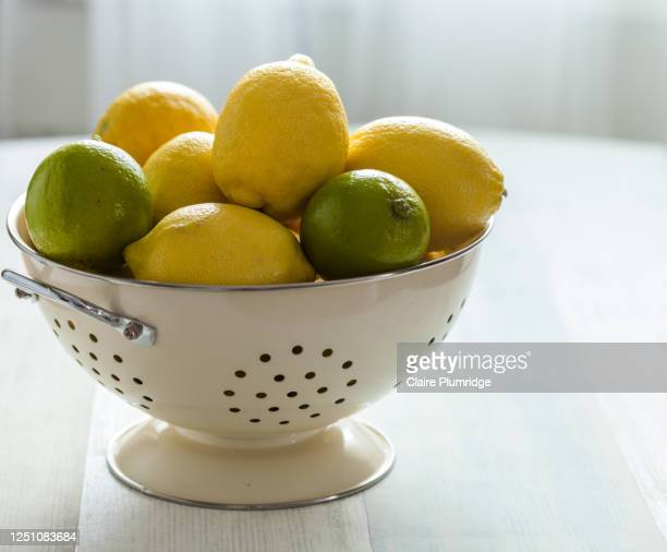 lemons and limes in a colander on a table - newbury england stock pictures, royalty-free photos & images