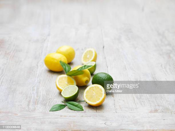 lemons and limes on whitewashed wooden table - whitewashed stock pictures, royalty-free photos & images