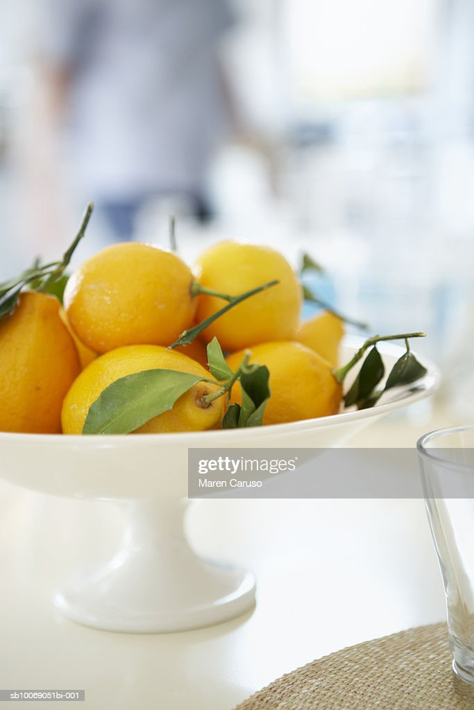 Lemons in bowl on table, person standing in backgroundclose-up : Stockfoto