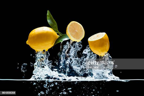 lemons jump out from water. - zitrone stock-fotos und bilder