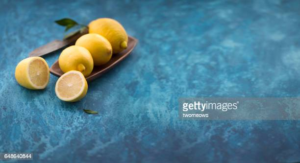 Lemons on rustic blue table top background.