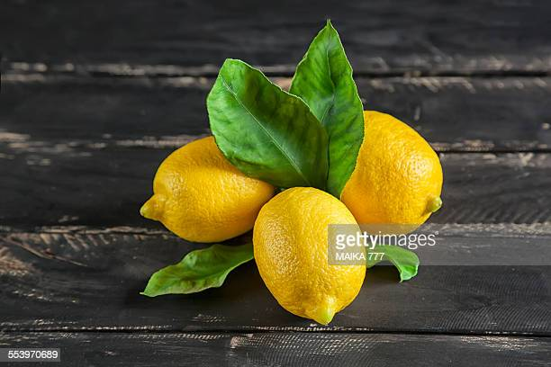 lemons with leafs on black wooden background - lemon leaf stock photos and pictures