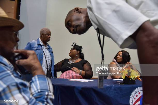 """Lena Butler, 2nd from L, chats with Shernita Jefferson and Deborah Simms - both of the DC Housing Authority - while Norman """"Bozo"""" Bowlding, L, is..."""