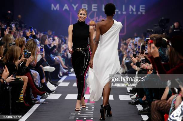 Lena Gercke and Herieth Paul walk the runway at the Maybelline New York show 'Makeup that makes it in New York' during the Berlin Fashion Week...