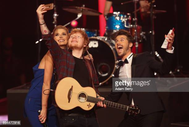 Lena Gercke Ed Sheeran and Thore Schoelermann take a selfie during the 'The Voice of Germany' finals at Studio Berlin Adlershof on December 17 2017...