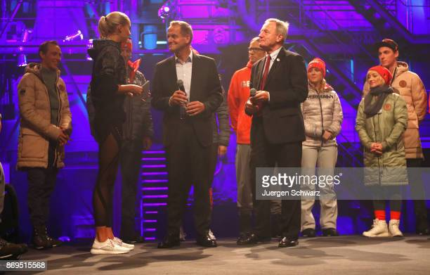 Lena Gercke stands close to Karl Quade and Fabian Fischer during the presentation of the outfit for German athletes competing in the upcoming Olympic...