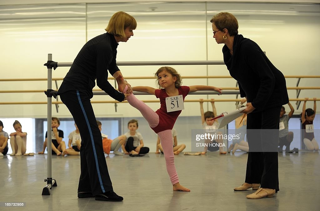 Lena Hecker (C) is tested for flexibility by Katrina Killian (L) and Kay Mazzo (R) as about 100 six-year-olds audition for spots in the School of American Ballet April 5, 2013 at Lincoln Center in New York.The audition is part of the spring recruiting season for new students. AFP PHOTO/Stan HONDA