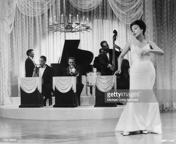 Circa 1950: Lena Horne performs on the set of a movie with Dexter Gordon on saxophone circa 1950 in Los Angeles, California.