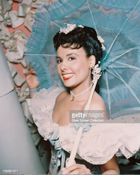 Lena Horne , US jazz singer and actress, wearing an off-the-shoulder dress with a white lace ruff over the shoulders, smiling while carrying a blue...