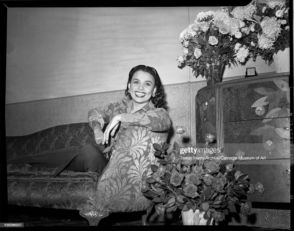 Lena Horne wearing patterned blouse and dark slacks, lounging on floral sofa at Stanley Theatre, with bouquets of flowers on right, Pittsburgh, Pennsylvania, 1944.