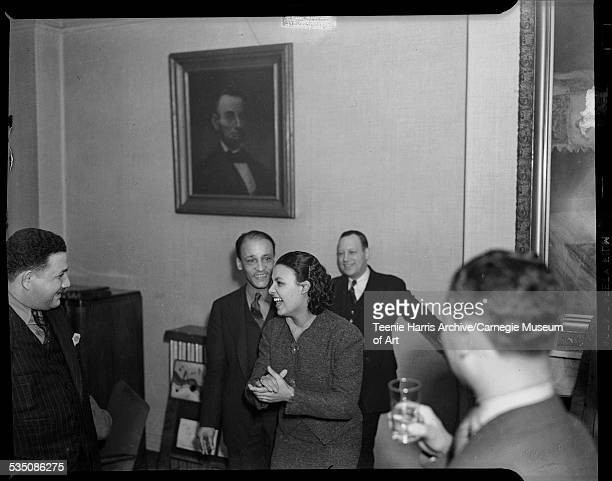 Lena Horne with hands clasped standing in middle of group of men including father Teddy Horne and Earl McDonald standing in background in Loendi Club...
