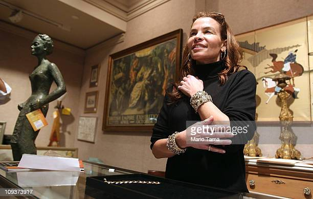 Lena Horne's granddaughter Jenny Lumet tries on a pair of Horne's cuff bracelets before they are auctioned at Doyle New York February 23 2011 in New...