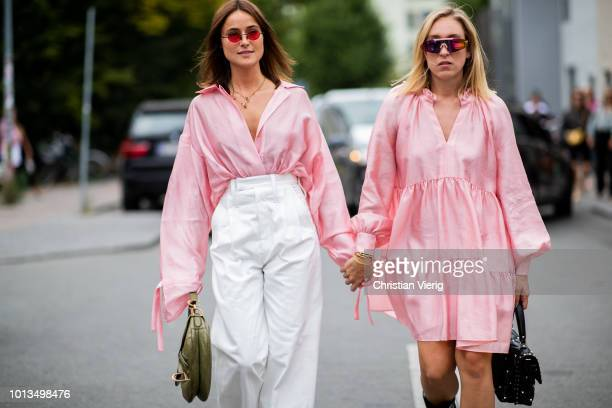 Lena Lademann and Sonia Lyson wearing pink dress Valentino bag boots is seen outside Stine Goya during the Copenhagen Fashion Week Spring/Summer 2019...