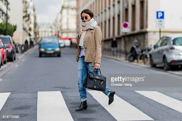 Lena Lademann is wearing Esprit beige jacket blue denim jeans black bag and boots creme scarf and Ray Ban sunglasses during the Paris Fashion Week...