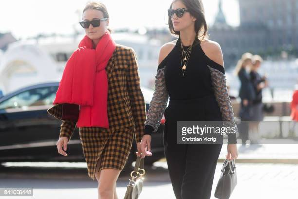 Lena Lademann wearing a red scarf, brown yellow checked coat and Darja Barannik wearing an off shoulder top outside Whyred on August 30, 2017 in...