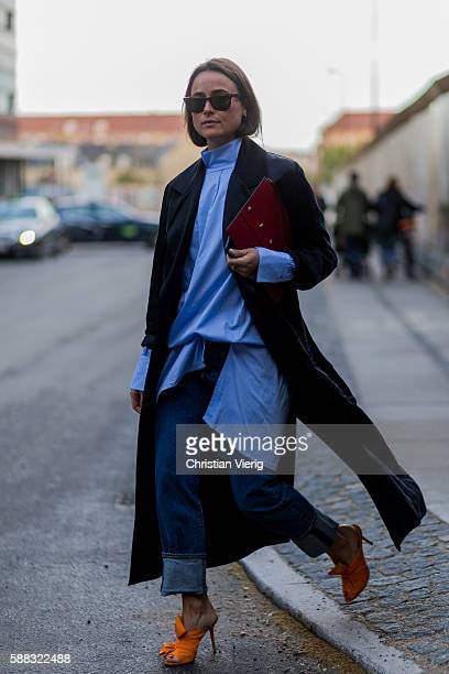 Lena Lademann wearing Charlotte Olympia shoes and a black trench coat and denim jeans outside Lala Berlin during the first day of the Copenhagen...