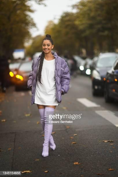 Lena Mahfouf aka Lena Situations wears a white long t-shirt dress, a purple shiny oversized puffer jacket from Miu Miu, pale purple shiny leather...