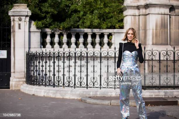 Lena Perminova wearing an holographic jumpsuit black heels and black bag is seen before the Balmain show on September 28 2018 in Paris France