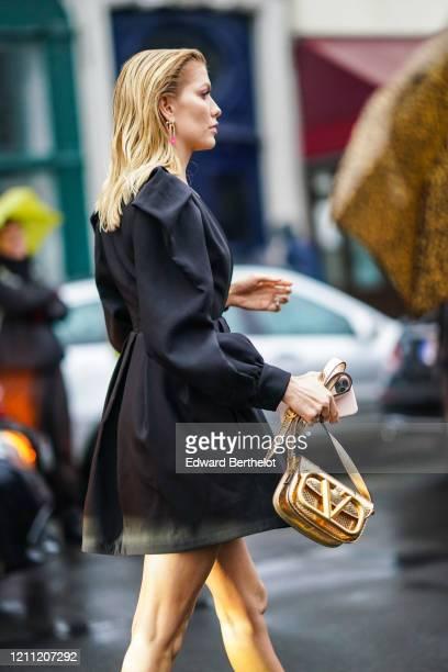 Lena Perminova wears a black dress, a golden Valentino bag, earrings, outside Valentino, during Paris Fashion Week - Womenswear Fall/Winter...
