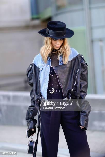 Lena Perminova wears a hat a blue denim jacket a black leather jacket flare pants during Paris Fashion Week Womenswear Fall/Winter 2018/2019 on March...