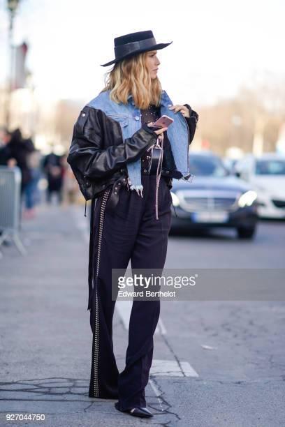 Lena Perminova wears a hat, a blue denim jacket, a black leather jacket, flare pants, during Paris Fashion Week Womenswear Fall/Winter 2018/2019, on...