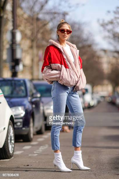 Lena Perminova wears a red and pink bomber jacket cropped jeans white shoes sunglasses outside Giambattista Valli during Paris Fashion Week...