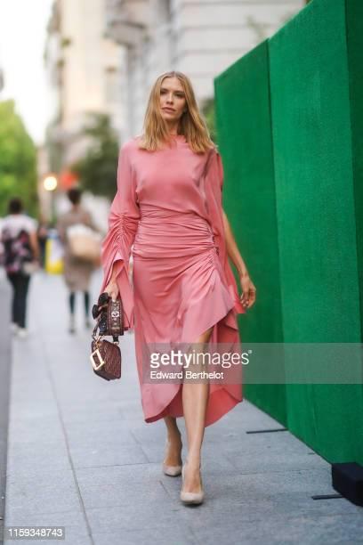 Lena Perminova wears a salmon-pink drape dress, a Christian Dior monogram bag, beige pointy heeled pumps, outside AMFAR dinner, during Paris Fashion...