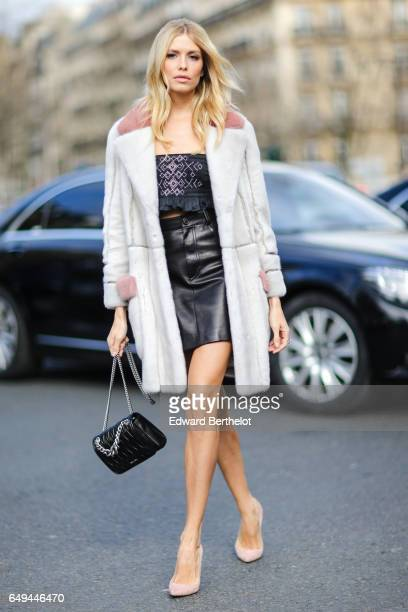 Lena Perminova wears a white coat a black sleeveless tshirt a black leather skirt pink shoes and a black bag outside the Miu Miu show during Paris...