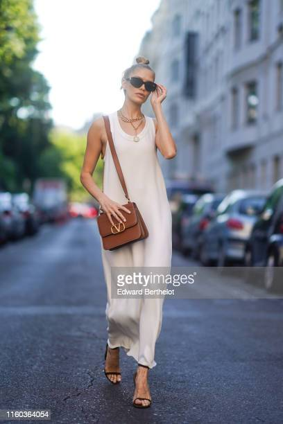 Lena Perminova wears a white dress, a brown Valentino leather bag, outside Valentino, during Paris Fashion Week -Haute Couture Fall/Winter 2019/2020,...