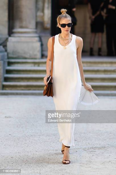 Lena Perminova wears a white dress a brown Valentino leather bag golden necklace sandals outside Valentino during Paris Fashion Week Haute Couture...