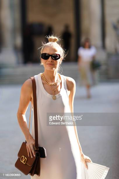 Lena Perminova wears a white dress, a brown Valentino leather bag, golden necklace, sandals outside Valentino, during Paris Fashion Week -Haute...