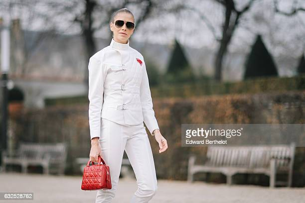 Lena Perminova wears a white jacket sunglasses white pants white shoes a red Dior bag and attends the Christian Dior Haute Couture Spring Summer 2017...