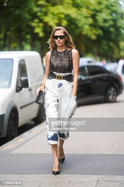 Lena Perminova wears black sunglasses, a golden bracelet, a black lace top, a large DIor belt, tie-and-dye white crop pants, a Dior monogram bag,...