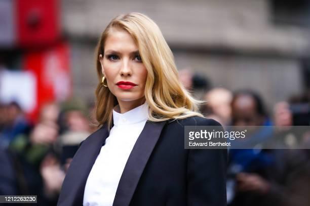 Lena Perminova wears earrings, a white shirt with a mandarin-collar, a black tuxedo jacket, outside Giambattista Valli, during Paris Fashion Week -...