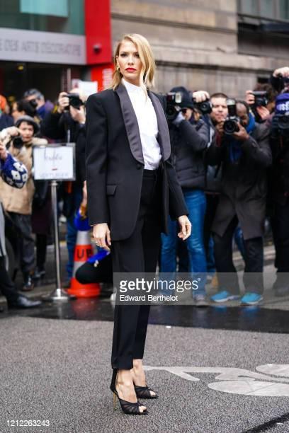 Lena Perminova wears earrings, a white shirt with a mandarin-collar, a black tuxedo jacket, black pants, black peep-toe heeled sandals, outside...